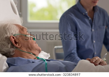 View of elder sick man being visited by his realtive - stock photo