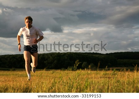 View of energetic man running in the forest - stock photo