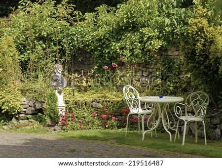 View of English country garden with table and chairs. - stock photo