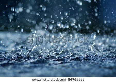 View of falling rain cast in a blue light. - stock photo