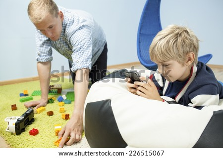 View of father cleaning son toys instead of him - stock photo