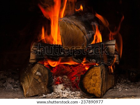 view of fireplace with burning logs within  - stock photo
