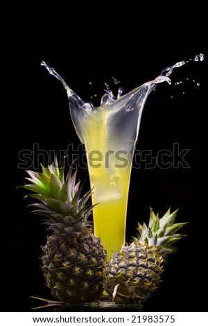 View of fresh pineapple juice splashing out of glass - stock photo