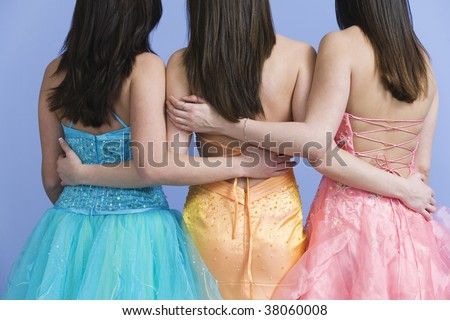 View of friends holding each other by the waist wearing prom dresses. - stock photo