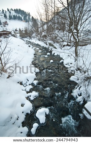 View of frozen river countryside. Brook in snowy landscape. Romanian small river in winter scenery, Romania, Moeciu. Wild brook in winter season. - stock photo