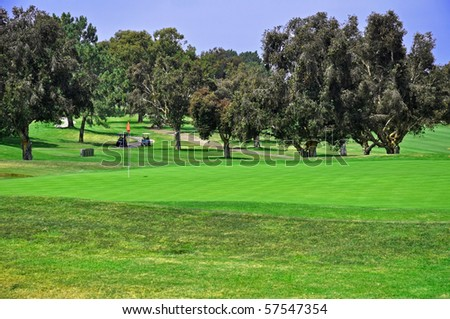 View of Golf Green with red flag in hole and two golf carts in the distance - stock photo
