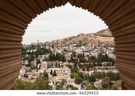 View of Granada through a moorish window of the Alhambra palace in Spain - stock photo
