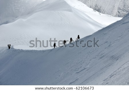 View of group hiking on slope of high Alps mountains. - stock photo