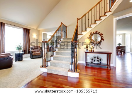 View of hardwood hallway with staircase and  living room with leather armchairs and table - stock photo