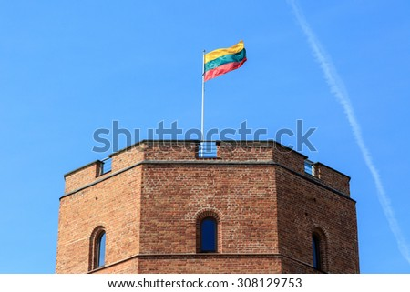 View of historical old  Gediminas Tower with lithuanian flag, on blue clear sky background. - stock photo