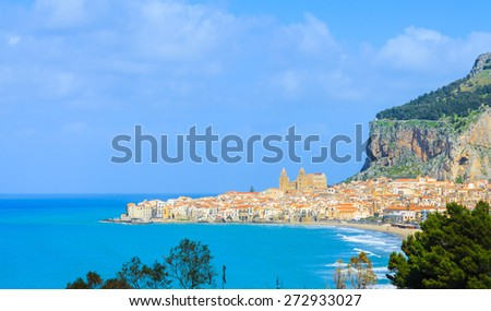 View of houses and church along the shoreline and mountain in background of Cefalu city, Sicily. - stock photo