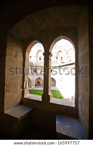 View of inner yard of Papal Palace (Palais des papes d'Avignon, circa 1370) via medieval window. UNESCO World Heritage Site. Avignon, France - stock photo