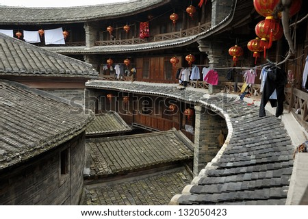 View of interior yard in traditional round Hakka building. In background a man is taking photograph. Wooden facade with some drying clothes. Fujian province. - stock photo