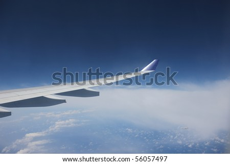 View of jet plane wing with cloud patterns - stock photo