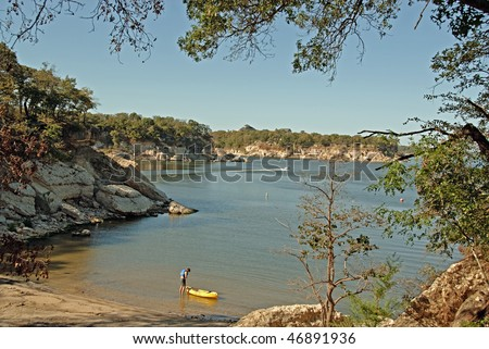 View of Lake Texoma at Eisenhower State Park outside Denison Texas and a man putting on his life vest to go kayaking. - stock photo