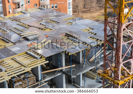 View of large high rise apartment building framework in the process of being constructed with crane tower in foreground - stock photo