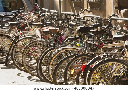 View of large number of Bicycles in racks on a sidestreet of Florence - stock photo