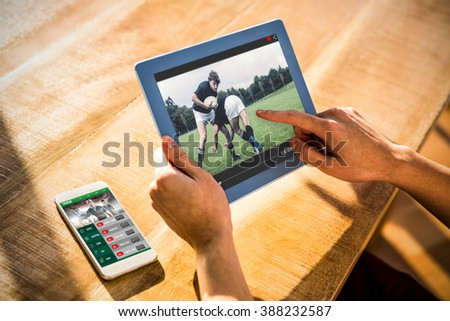 View of lecture app against over shoulder view of casual man using tablet - stock photo