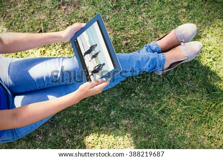 View of lecture app against woman using tablet in park - stock photo