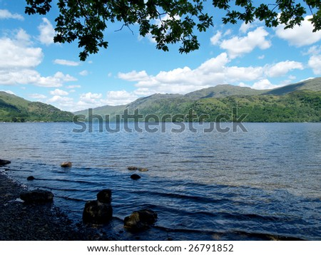 View of Loch Lomond from shoreline under trees - stock photo