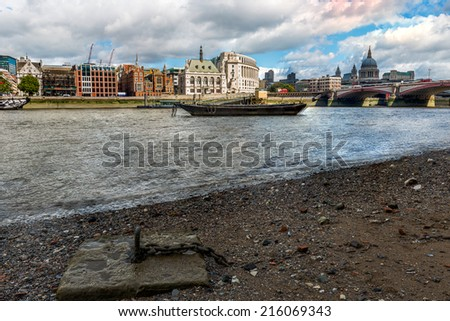 View of London city skyline during low tide on River Thames - stock photo
