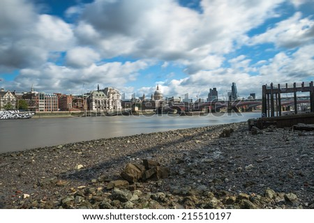 View of London city skyline including St Paul's Cathedral during low tide on River Thames - long exposure - stock photo