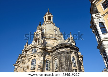 View of Lutheran Frauenkirche church (Church of Our Lady) on background of bright blue sky from the corner of Rampiche Street in Dresden, Saxony, Germany. - stock photo