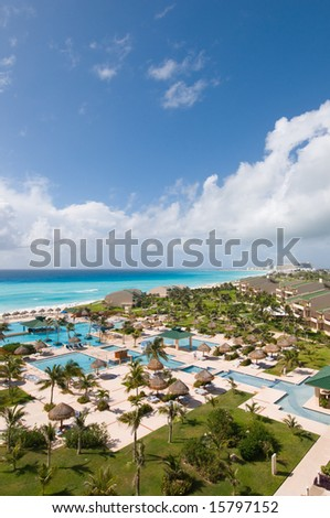 View of luxury tropical oceanfront resort with pools and lush landscaped grounds - stock photo