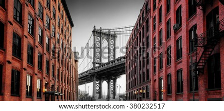 View of Manhattan Suspension Bridge Supportive Arch in Black and White Framed by Colorized Brick Buildings on Washington Street in Brooklyn, New York City, New York, USA - stock photo