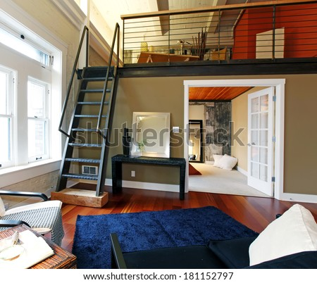 View of modern reconstructed living room with mezzanine area above bedroom. View of iron steep stairs - stock photo