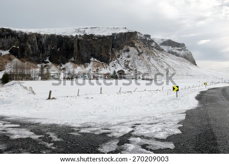 View of mountains, snow covered plains and rivers in the countryside farm lands in southern Iceland. - stock photo