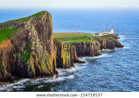 View of Neist Point lighthouse and rocky ocean coastline, highlands of Scotland - stock photo