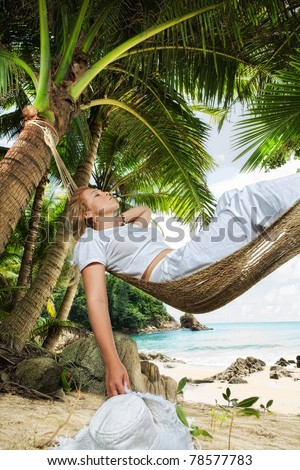 view of nice woman lounging in hammock in tropical environment - stock photo