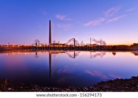 View of nickel plant with big and tall chimney during sunrise - stock photo