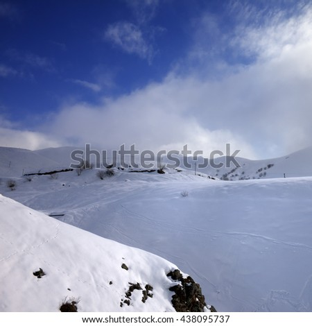 View of off-piste slope and mountains in haze. Caucasus Mountains, Georgia, region Gudauri. - stock photo