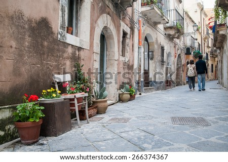 View of one typical street in Ortigia, the old part of Syracuse, and some ornamental flowered vases in the foreground and a couple walking - stock photo