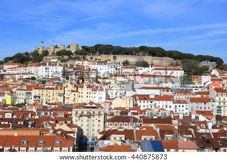 View of over the rooftops of Lisbon from the top of the Santa Justa Elevator towards Castelo de San Jorge. - stock photo