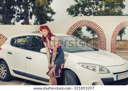 View of pinup young woman in vintage style clothing next to a white car. - stock photo