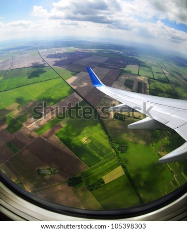 View of plane wing with cloud patterns  and earth - stock photo