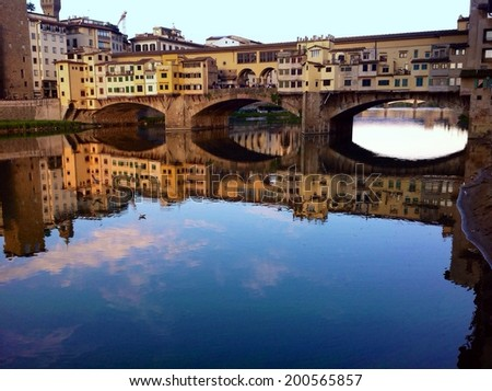 View of Ponte Vecchio in Florence with scenic water reflections - stock photo