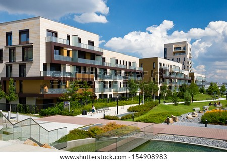 View of public park with newly built modern block of flats under blue sky with few clouds - stock photo