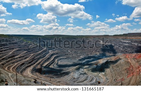 view of  quarry extracting iron ore with heavy trucks, excavators, diggers and locomotives - stock photo