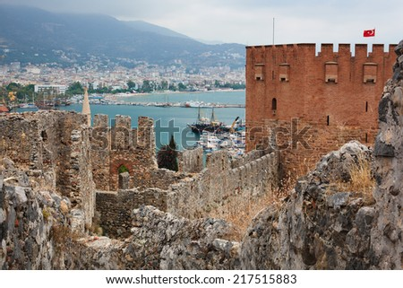 View of Red Tower (Kizil Kule) and ancient stone wall of Alanya Castle, Turkey - stock photo
