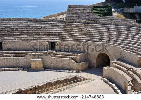 View of roman amphitheater against sea in Tarragona, Spain. - stock photo