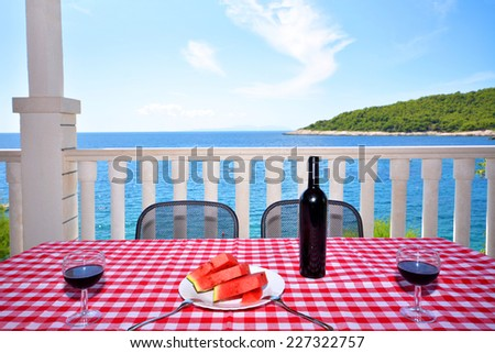 View of sea and blue sky from terrace in Hvar, Croatia. Chilled watermelon and black wine with two wineglass on the table. - stock photo