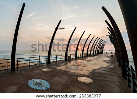 View of ships on Indian Ocean through the Millenium Pier in Umhlanga Rocks at sunrise - stock photo