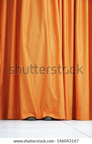 View of shoes seen hiding behind orange curtain - stock photo