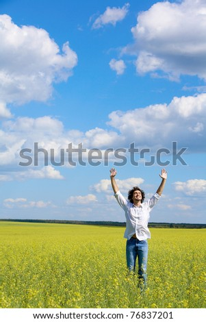 View of smiling man raising his hands while standing in the field - stock photo