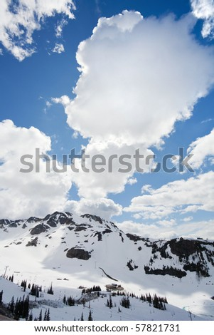 View of snow-covered mountains and dramatic clouds from Whistler Peak in British Columbia, Canada vertical - stock photo