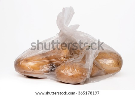 View of some bananas inside a plastic bag isolated on a white background. - stock photo
